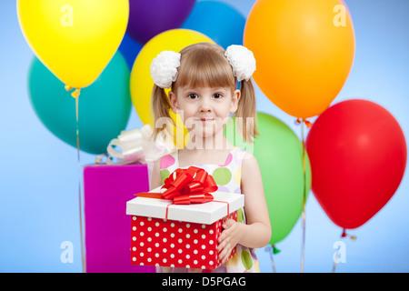 Fille mignonne avec des ballons colorés et cadeaux Banque D'Images