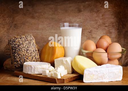 La vie toujours avec les produits laitiers, lait, œufs, pain et fromage sur un fond de bois vintage