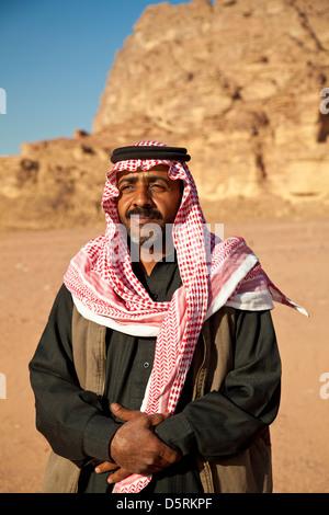 Un Bédouin homme portant le rouge et blanc foulard keffieh à damier dans le Wadi Rum, Jordanie Banque D'Images