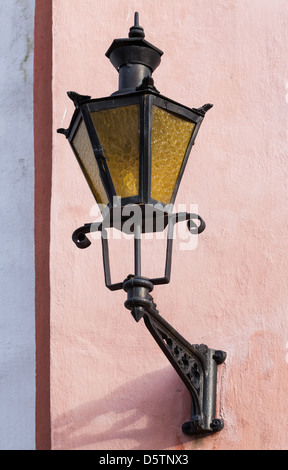 Ancienne lanterne sur le mur d'un bâtiment rose à Tallinn, Estonie Banque D'Images
