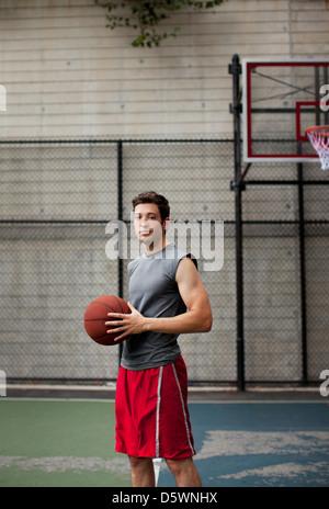 Homme debout sur un terrain de basket-ball Banque D'Images