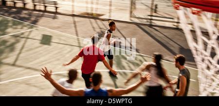 Les hommes jouant au basket-ball sur cour Banque D'Images