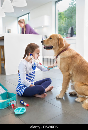 Girl playing doctor with dog in kitchen Banque D'Images