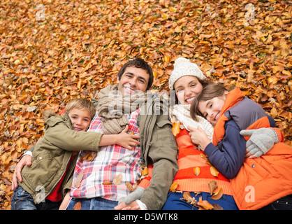 Smiling family fixant dans les feuilles d'automne Banque D'Images