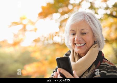 Femme plus âgée using cell phone in park Banque D'Images