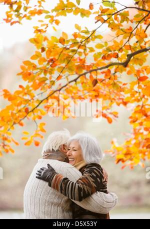Vieux couple hugging in park Banque D'Images