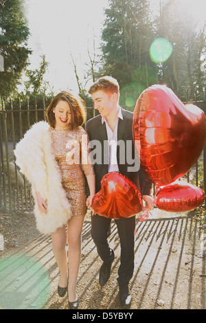 Young Couple in Park Holding Heart Shaped Balloons Banque D'Images