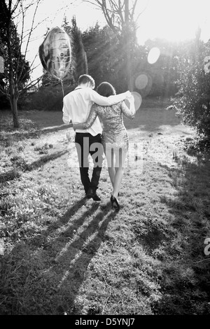 Couple in Park Holding Heart Shaped Balloon, vue arrière Banque D'Images