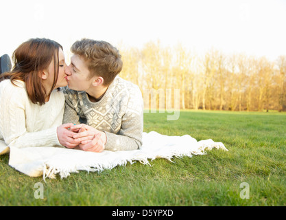 Jeune couple lying on Grass Kissing Banque D'Images