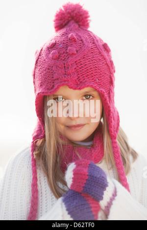 Portrait of a cute young girl in pink hat et de vêtements d'hiver sur plage de Hunstanton, Norfolk, UK Banque D'Images