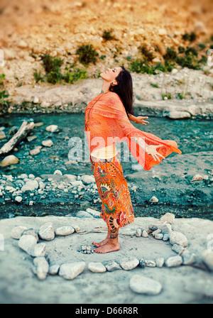 Femme à l'extérieur près d'une rivière avec ses bras et cœur ouvert dans un mandala de pierres. Banque D'Images