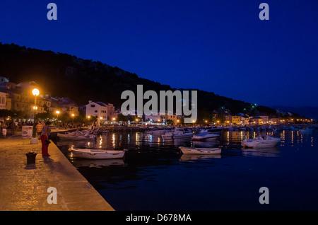 Un bateau au clair de lune dans la baie du port de la ville de Baska. Réflexions de l'eau à partir de l'éclairage Banque D'Images