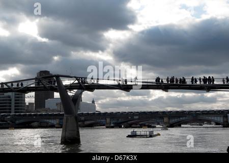 Une vue de côté la silhouette des piétons circulent sur le Millennium Bridge sur la Tamise Londres KATHY DEWITT Banque D'Images