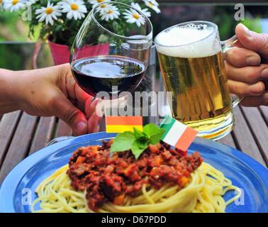 ILLUSTRATION - Une photo montre un homme et une femme clinking glasses de vin rouge italien et de la bière allemande Banque D'Images