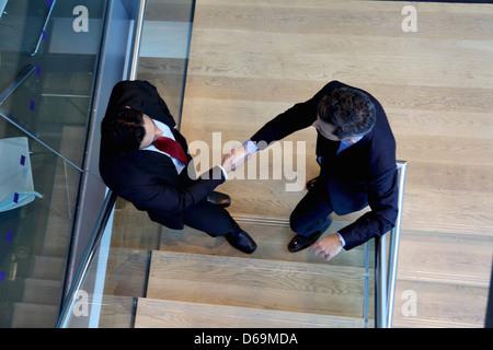 Businessmen shaking hands in office Banque D'Images