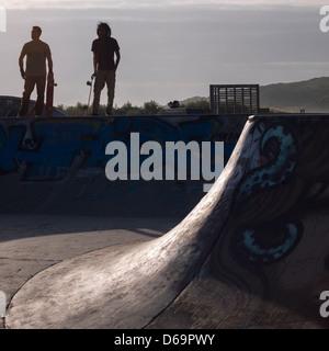 Hommes debout au bord de la rampe de skate Banque D'Images