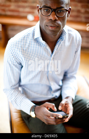 Businessman using cell phone in lobby Banque D'Images