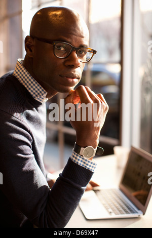 Businessman using laptop in cafe Banque D'Images