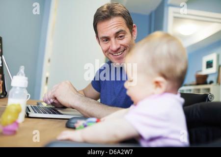 Baby Girl sitting avec le père au travail Banque D'Images