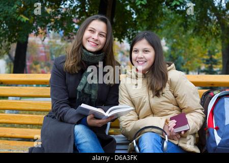 Deux jeunes filles lisant dans un parc Banque D'Images