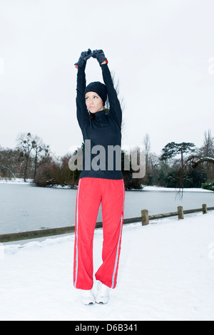 Runner stretching in snowy field Banque D'Images