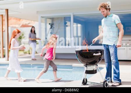 Les filles autour de la piscine comme père des barbecues Banque D'Images