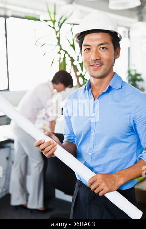 Businessman with blueprints in office