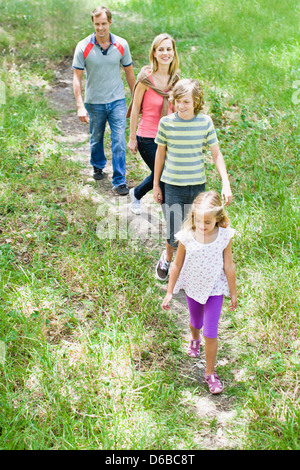 Family walking together in grass Banque D'Images