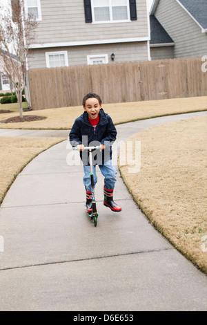 Mixed Race boy playing sur scooter sur rue de banlieue Banque D'Images