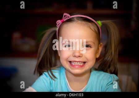Une fillette de cinq ans, s'assied à la table de la maison de ses parents et de sourires dans Sieversdorf, Allemagne, Banque D'Images