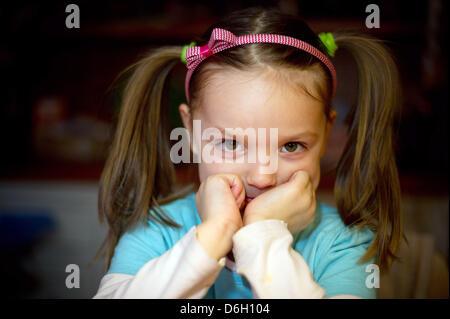 Une fillette de cinq ans, s'assied à la table de la maison de ses parents et se penche sur l'appareil photo de Sieversdorf, Banque D'Images