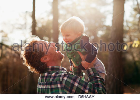 Father carrying son in park Banque D'Images