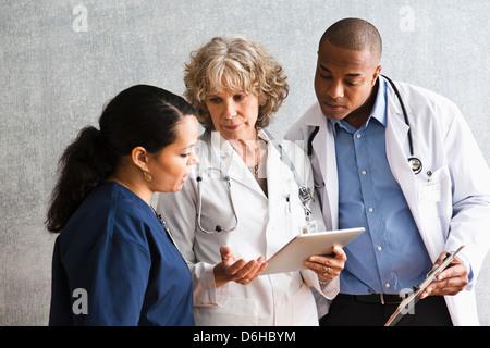 Les infirmières et médecins qui parlent avec digital tablet Banque D'Images