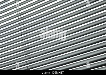 Les stores métalliques semi-fermé sur une fenêtre, motif à rayures en diagonale. Banque D'Images