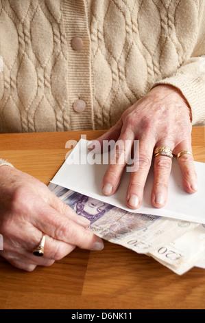 Femme âgée de 20 livres mettre des notes dans une enveloppe Banque D'Images