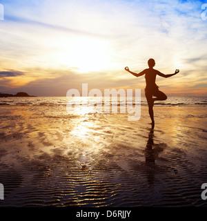 Bien-être concept, magnifique coucher de soleil sur la plage, woman practicing yoga Banque D'Images