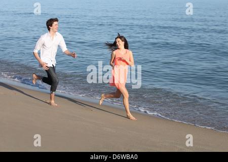 Couple d'adolescents en marche et le flirt sur la plage rive près de l'eau Banque D'Images
