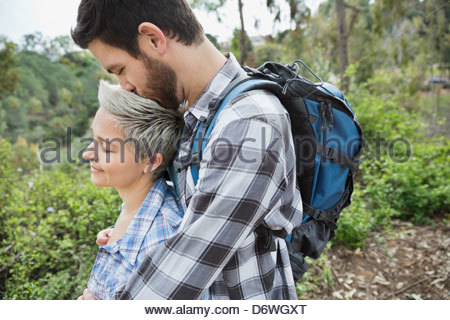 Side view of man kissing woman on head in forest Banque D'Images