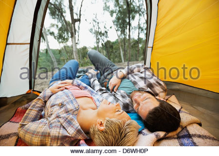 Heureux couple lying down together in tent Banque D'Images