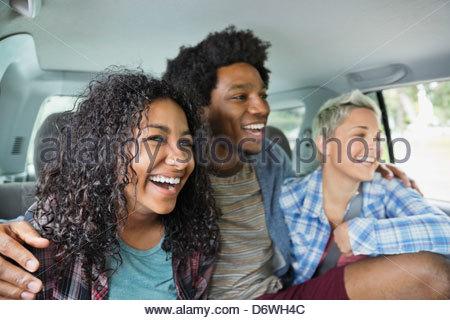 Heureux jeune homme avec bras autour de female friends sitting in truck Banque D'Images