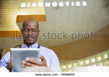 Mid adult male doctor using digital tablet in clinic Banque D'Images