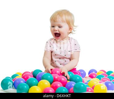 Portrait of a smiling infant assis parmi les boules colorées Banque D'Images