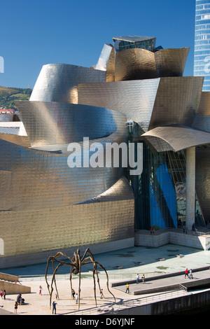 Les touristes au Guggenheim Museum voir l'araignée géante en bronze sculpture 'maman' à Bilbao, Espagne Banque D'Images