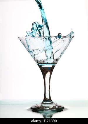 Verre à martini à l'alcool splash macro close up on white background Banque D'Images