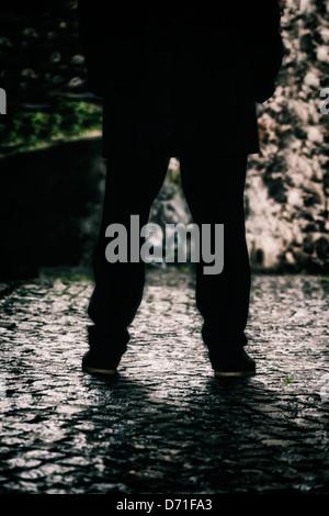 Les jambes d'un homme dans une ruelle sombre Banque D'Images