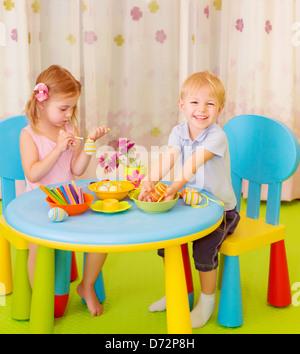 Petit frère et sœur s'amusant dans une garderie, symbole traditionnel de Pâques peinture art, belle leçon sur les Banque D'Images