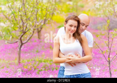 Happy young couple hugging in spring park, appréciant chaque printemps, d'autres nature, fleurs violettes, la tendresse Banque D'Images