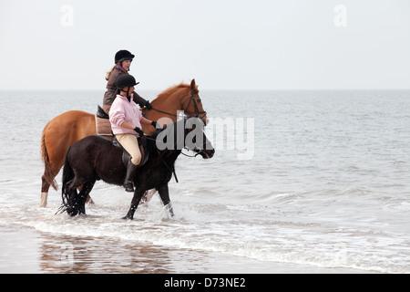 Deux jeunes femmes de l'équitation dans la mer surfez au bord de l'eau, Holkham Beach Norfolk, UK Banque D'Images