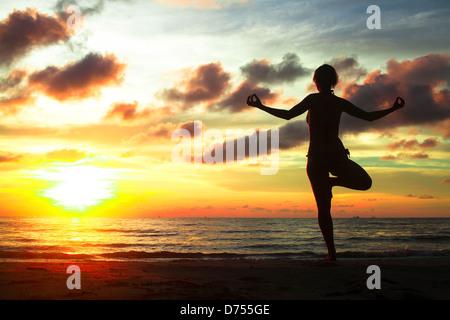Young woman practicing yoga sur la plage au coucher du soleil.