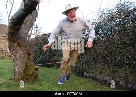74 ans grand-père sautant autour d'un parcours dans le jardin familial Banque D'Images
